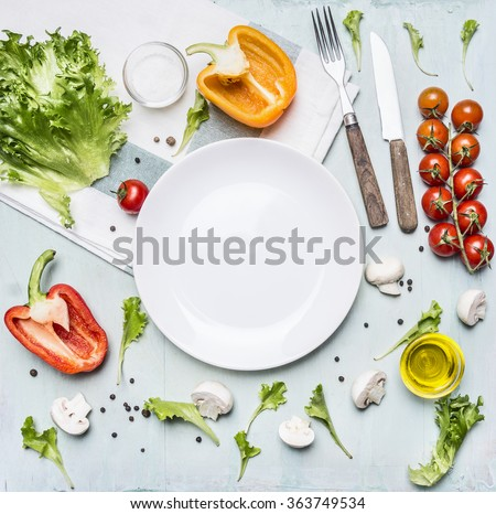 Ingredients for cooking salad cherry tomatoes, lettuce, peppers, spices and oil  laid out around a white plate on wooden rustic background top view close up