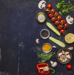 Ingredients for cooking vegetarian food tomatoes on a branch, herbs, cucumber, lemon, garlic, oil, black pepper, paprika, mushrooms, border ,with text area on wooden rustic background top view