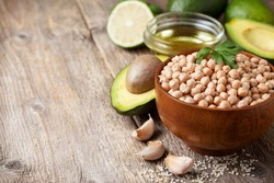 Ingredients for cooking with avocado hummus: chickpeas, avocados, olive oil, sesame, garlic, lime on the old wooden background