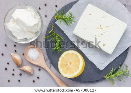 Ingredients for feta, cream cheese, rosemary, lemon and garlic dip on slate board, top view