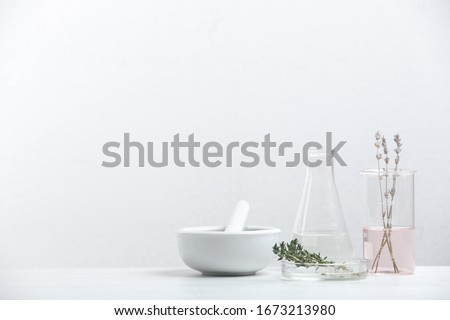 Ingredients for herbal cosmetic products and  laboratory glassware on white table. Space for text