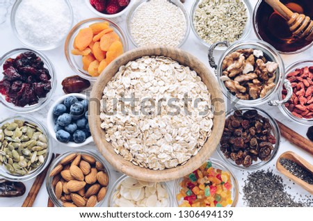 Ingredients for homemade granola: oats, chia, hemp and pumpkin seeds, cranberries and almonds, coconut and agave nectar, goji berries and fresh blueberries. Superfood. Top view. Flat lay.