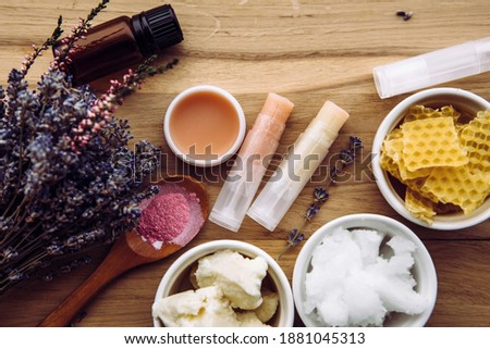 Ingredients for homemade lip balm: shea butter, essential oil, mineral color powder, beeswax, coconut oil. Homemade lip balm lipstick mixture with ingredients scattered around.
