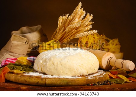 ingredients for homemade pasta on wooden table on brown background
