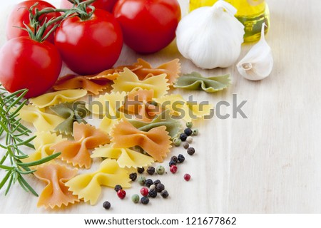 Ingredients for Italian cuisine: bow tie pasta, tomatoes, olive oil, rosemary, garlic and pepper. selective focus