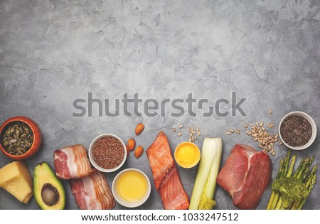 Ingredients for ketogenic diet: meat, bacon, fish, broccoli, asparagus, avocado, mushrooms, cheese, sunflower seeds, chia seeds, pumpkin seeds, flax seeds. view from above. copy space. toning #1033247512