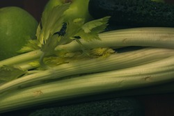 Ingredients for making a morning smoothie. Green celery stalks and juicy apples. Healthy food for a healthy lifestyle