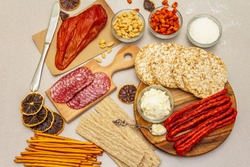 Ingredients for making charcuterie chalet. Set of various products for newest Christmas food trend. New Year holiday house building, stone concrete background, top view