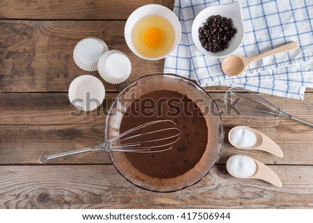 Ingredients for making cup cake chocolate on wooden background. #417506944