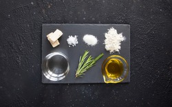 Ingredients for making focaccia - traditional Italian bread consist of yeast, Fleur de sel, sugar, flour, water, rosemary, olive oil - top view on the black background