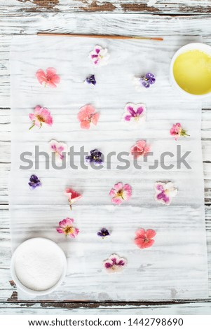 Ingredients for making homemade sugared or crystallized edible flowers on a white wooden rustic table. Image shot for above.