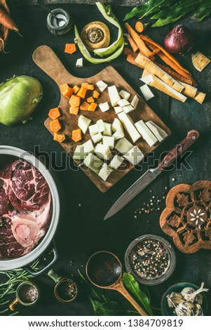 Ingredients for meat dishes recipes on kitchen table background with vegetables , seasoning and kitchen utensils, top view. Flat lay. Broth, meat bone stock or soup cooking preparation