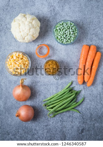 Ingredients for onion curry paste on light grey background. Picture of two onions, cauliflower, peas, corn, green beans and carrots on grey background.