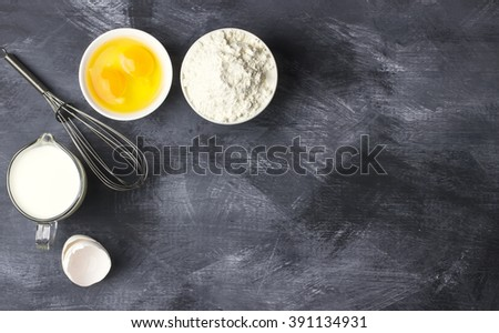 Ingredients for pastries: flour, eggs, milk against a dark background