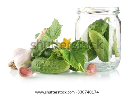 Ingredients for pickling or preserves cucumbers with flower bud,leaves,jar,garlic,dill flowers and tendrils isolated on white background