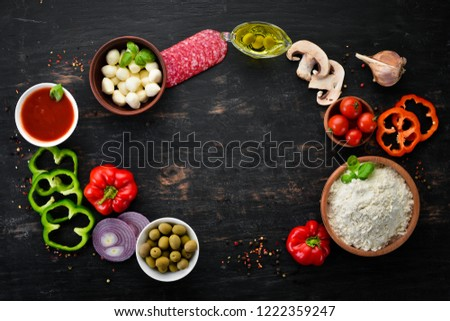 Ingredients for pizza. Mushrooms, sausages, tomatoes, vegetables. Top view. On a black wooden background. Free copy space.