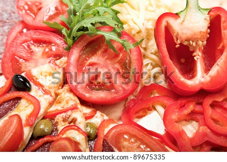 Ingredients for pizza. Tomato, cheese, paprica and salami