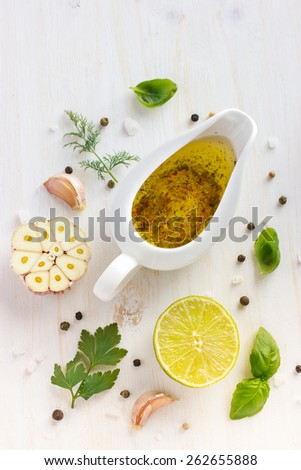 Ingredients for salad dressing. Olive oil, garlic, lemon, herbs and spices on white background, top view