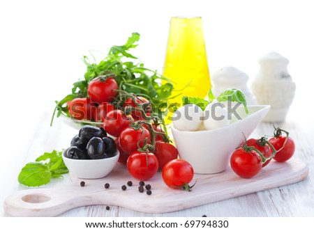 Ingredients for salad  with mozzarella, tomatoes,black olives,rocket and olive oil