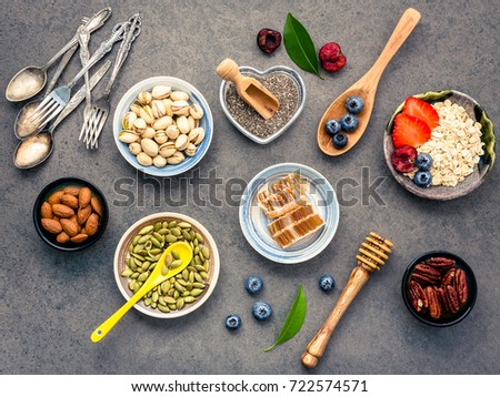 Ingredients for the healthy foods background Mixed nuts, honey, berries, fruits, blueberry, orange, almonds, oatmeal and chia seeds .The concept of healthy food set up on dark stone background. #722574571