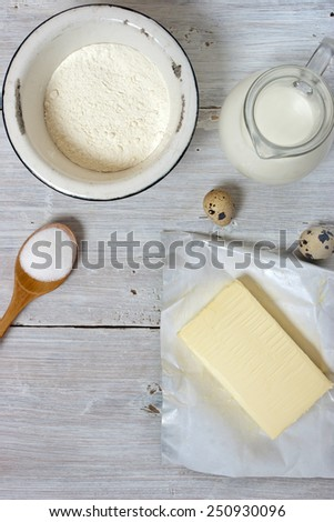 Ingredients for the pancakes on the white wooden table around the parchment roll
