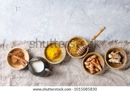 Ingredients for turmeric latte. Ground turmeric, curcuma root, cinnamon, ginger, honeycombs in wooden bowls, jug of milk over grey texture background with textile linen. Top view, copy space #1015085830