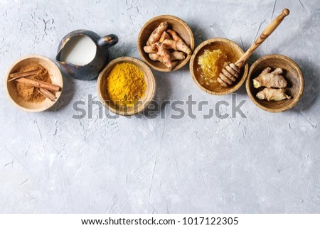 Shutterstock Ingredients for turmeric latte. Ground turmeric, curcuma root, cinnamon, ginger, honeycombs in wooden bowls, jug of milk over grey texture background. Top view, copy space