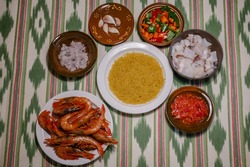 ingredients to make a fideuá on a table: onion, noodles, garlic, tomato, peppers, cuttlefish and prawns