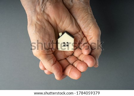 Inheritance concept. Elderly woman hands holds a little toy house. Inherited property idea.