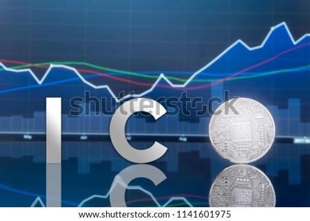 Initial coin offering (ICO) and digital token investing concept - Physical metal digital coins with blue global trading exchange market price chart in the background.