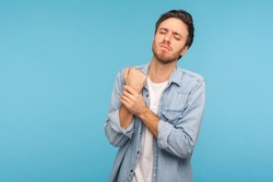 Injured arm. Portrait of office worker man in denim shirt touching painful hand, suffering trauma, sprain wrist, feeling ache of carpal tunnel syndrome. indoor studio shot isolated on blue background