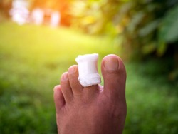 injured big toe with bandage on blur background with sunlight.