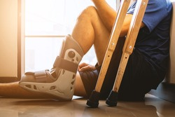 injured man broken ankle wearing ankle support sitting in the house with soft-focus and  over light in the background
