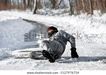 Injured man lying on the road, downfall and accident on winter season, black ice  stock photo