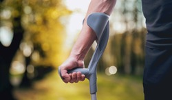 Injured man trying to walk on crutches. Blurred background