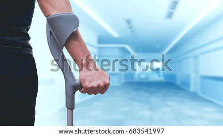 Injured man trying to walk on crutches. Blurred background - Shutterstock ID 683541997