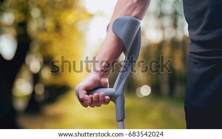 Injured man trying to walk on crutches. Blurred background #683542024