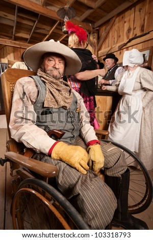 Injured mature cowboy in wheelchair at old west saloon