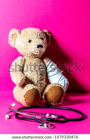 injured teddy bear with a bandage and stethoscope at the foreground for child education to healthcare or mishap over pink background  #1479330476