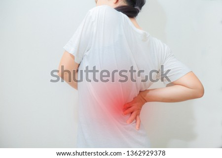 injury Asian woman stretches back pain backache, spinal .  cause of  Long working hours and health.