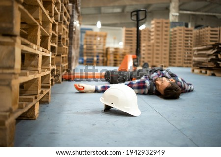 Injury at work. Warehouse worker lying unconscious on the concrete floor after the fall. Stockfoto ©