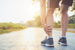 Injury from workout concept : The asian man use hands hold on his ankle while running on road in the park. Focus on ankle.