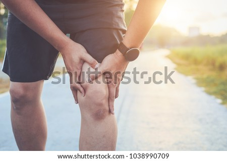 Photo of  Injury from workout concept : The asian man use hands hold on his knee while running on road in the park. Shot in morning time, sunlight and warm effect with copy space for text or design