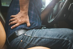 Injury or tired from long driving concept : Man use hands hold and massage on his back in the car while stop. Outdoor shooting for transport and healthcare