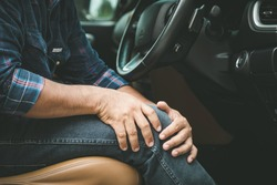 Injury or tired from long driving concept : Man use hands hold and massage on his knee in the car while stop. Outdoor shooting for transport and healthcare