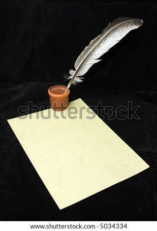 ink bottle and a quill on an old paper