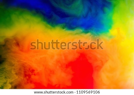 Stock Photo Ink in the water. A splash of Multicolor red, blue, yellow and green paint. Abstract background