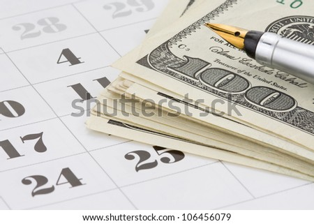 ink pen and dollar money on calendar background