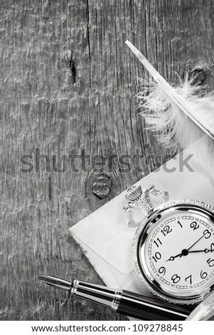 ink pen and watch on wooden background