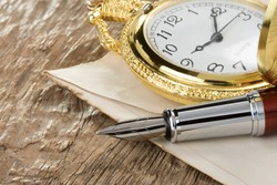 ink pen and watch on wooden notebook